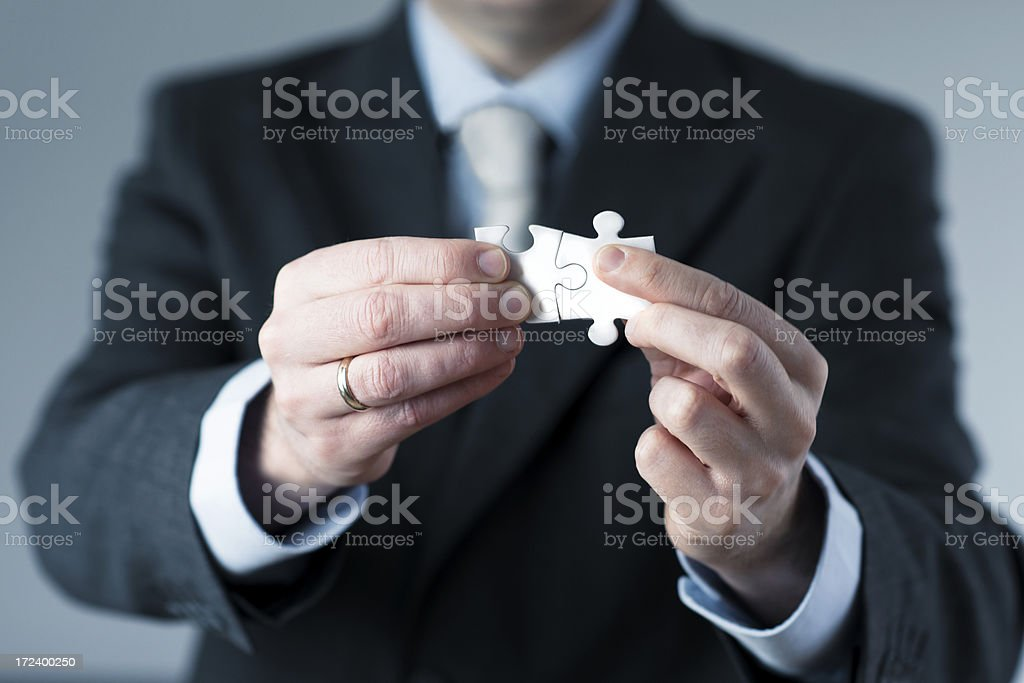 Man in suit connects two jigsaw puzzles royalty-free stock photo