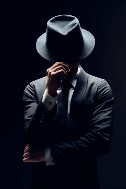 Mann in Anzug versteckt Gesicht hinter seinem Hut isoliert auf dunklem Hintergrund – Foto