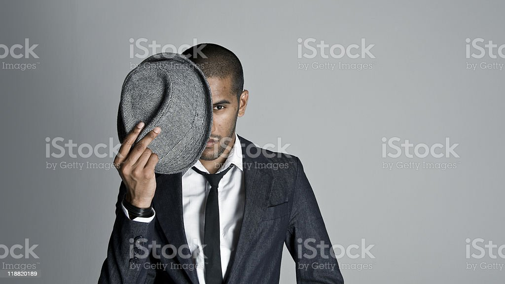Man in suit hiding his face behind a hat isolated on gray royalty-free stock photo
