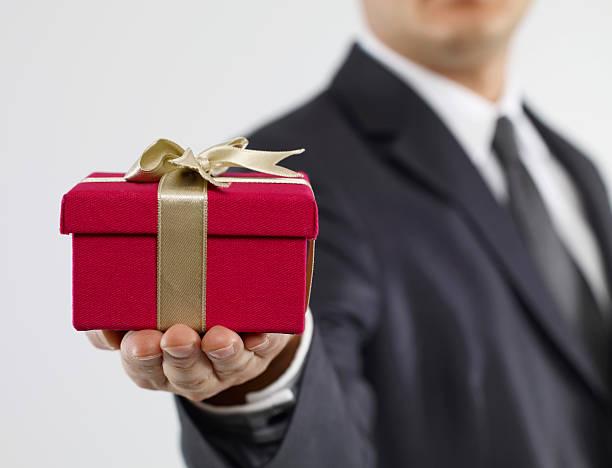 Mann im Anzug hält eine rote Geschenkbox mit gold Schleife – Foto
