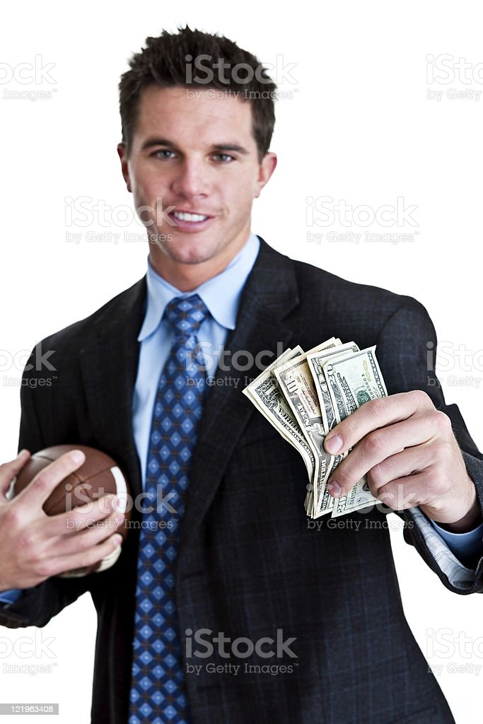 Man in suit holding cash and football royalty-free stock photo