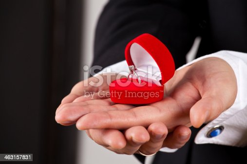 istock Man in suit holding engagement ring 463157831