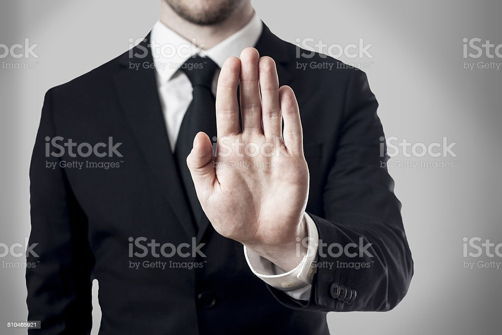 man in suit holding hand stop stock photo