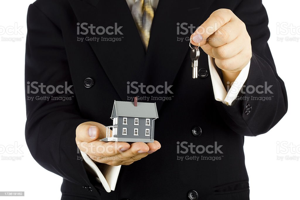 Man in suit holding house and keys royalty-free stock photo