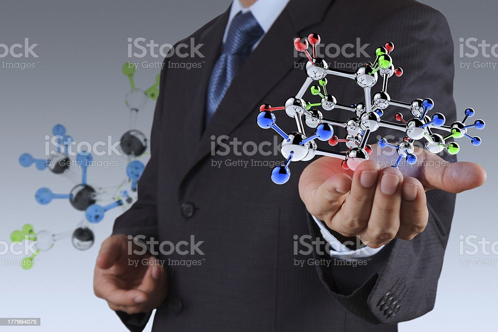 Man in suit holding molecule model in hand businessman holding a molecule as science concept Adult Stock Photo