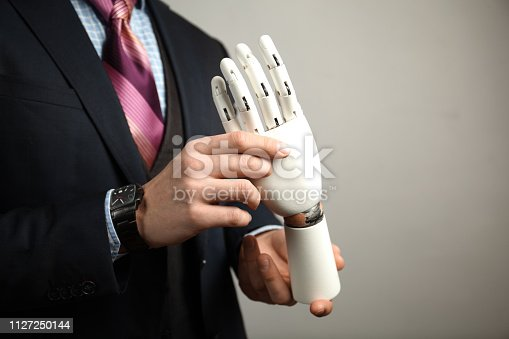 istock Man in suit holding prosthesis artificial man's hands 1127250144