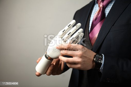 istock Man in suit holding prosthesis artificial man's hands 1129304856