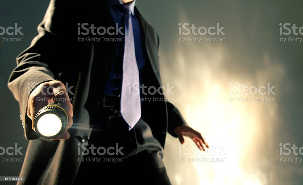 Man in Suit Holding Torch stock photo