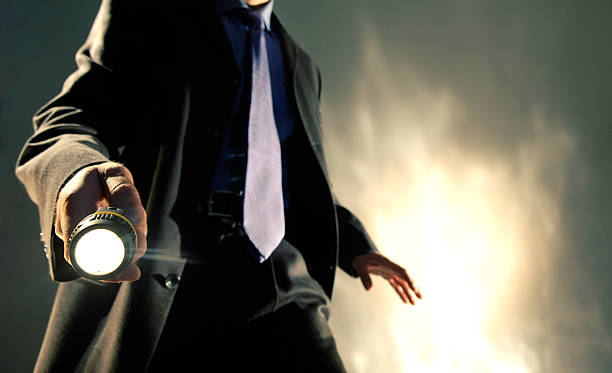 Man in Suit Holding Torch A close up of the torso of a Caucasian man dressed in a dark business suit, shirt and tie holding a battery operated torch pointed towards the camera, with his arm out in a dramatic pose. The man is standing against dark background with a brightly lit abstract pattern.  detective stock pictures, royalty-free photos & images