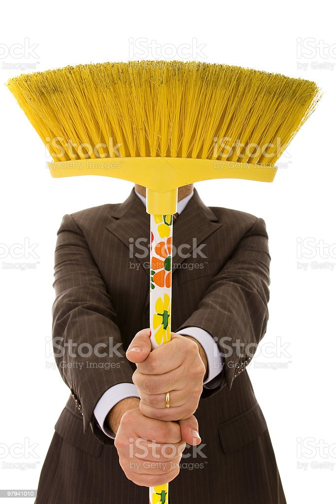 Man in suit holding up the broom as if he is going to sweep royalty-free stock photo