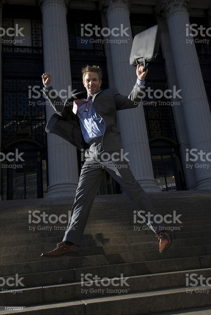 Man in Suit Leaps with Attache Case on Steps stock photo
