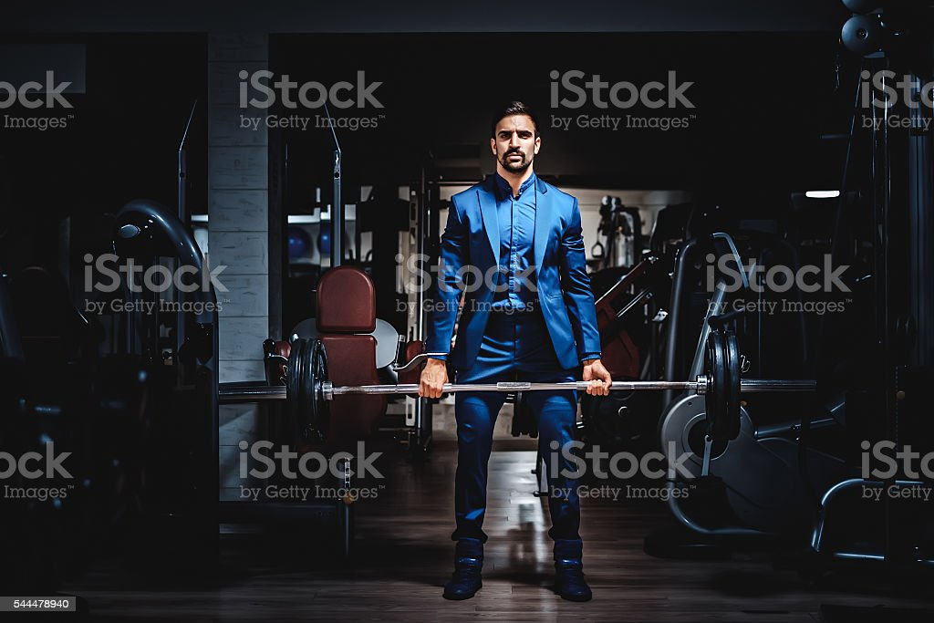 Man in suit lifting heavy weight stock photo