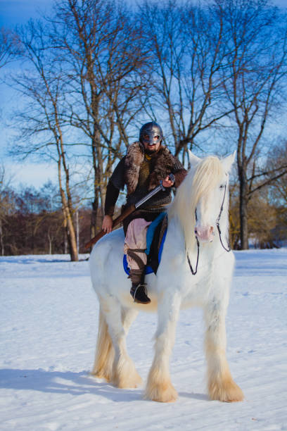 Man in suit of ancient warrior riding big white horse stock photo