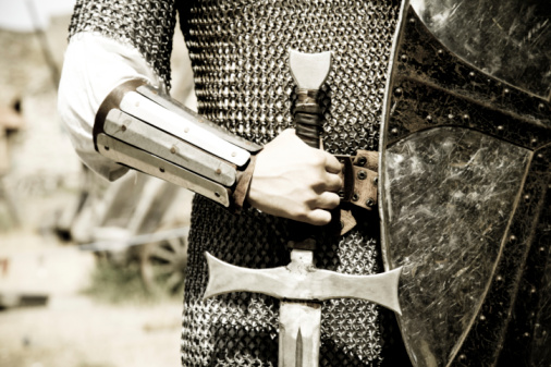 Man in suit of armor with medieval sword