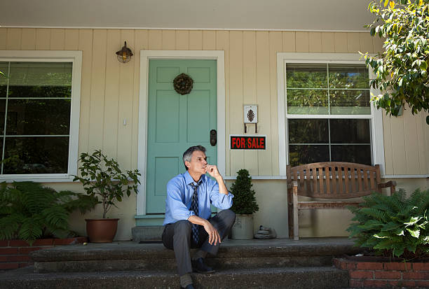 Man in suit outside home being foreclosed stock photo