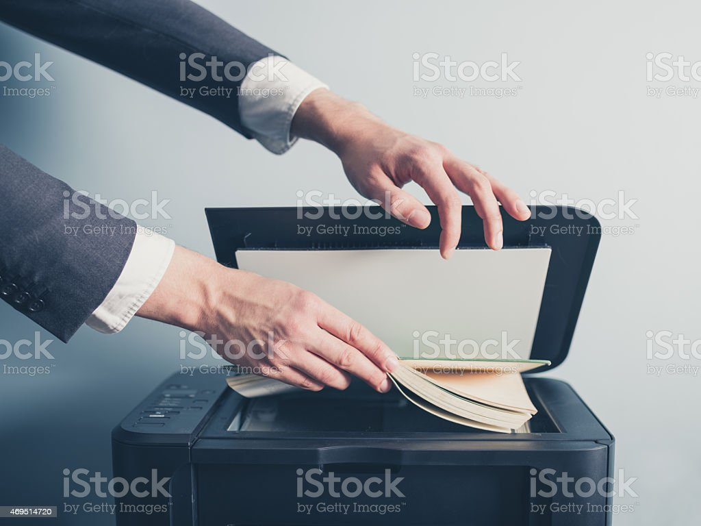 Man in suit photocopying a book stock photo
