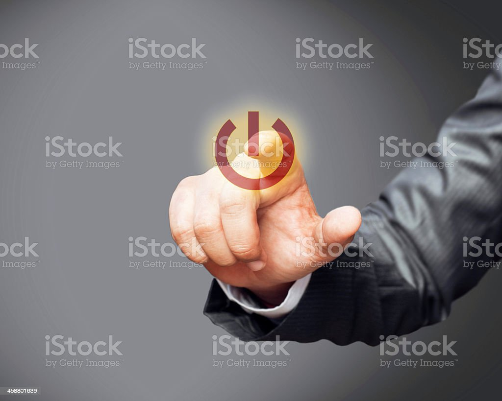 Man in suit pressing a red power button stock photo
