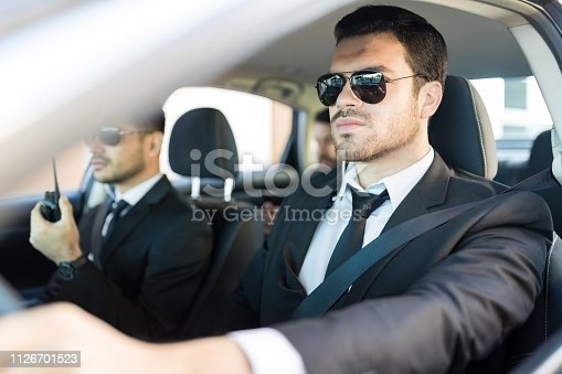 istock Man In Suit Providing Security To Boss During Journey 1126701523