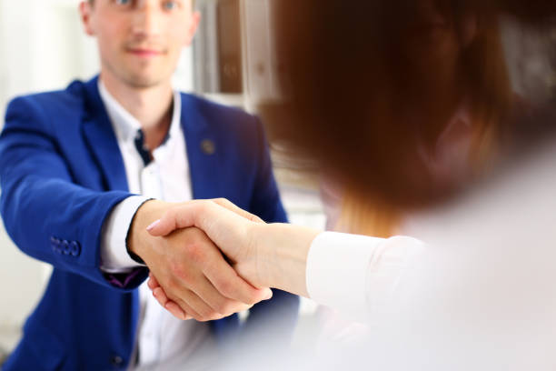 Man in suit shake hand as hello in office closeup stock photo