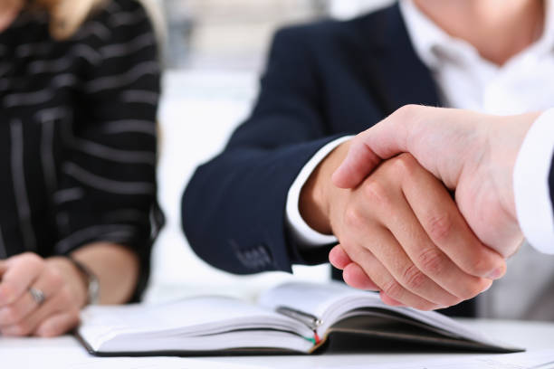 man in suit shake hand as hello in office closeup - financial advisor with clients stock photos and pictures