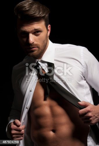 471947536 istock photo Man in suit showing abs as result of hard workout 487924259