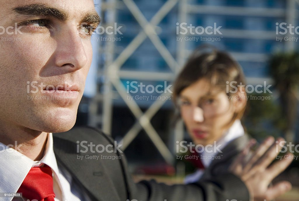 Man in suit showing his palm to a woman in a suit stock photo