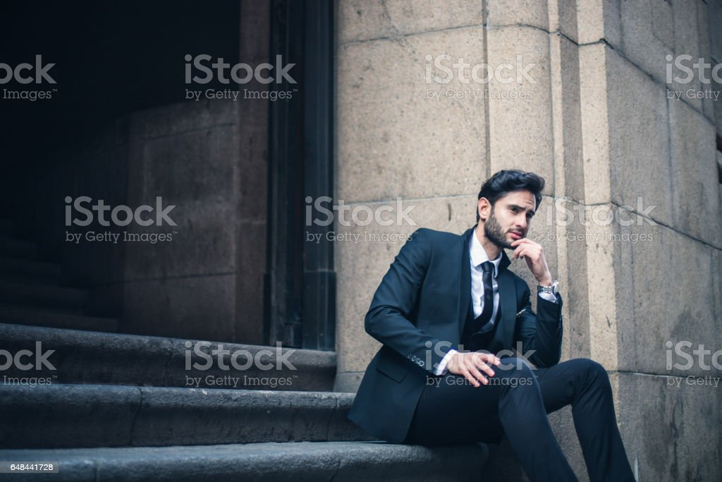 Man in suit sitting on steps stock photo