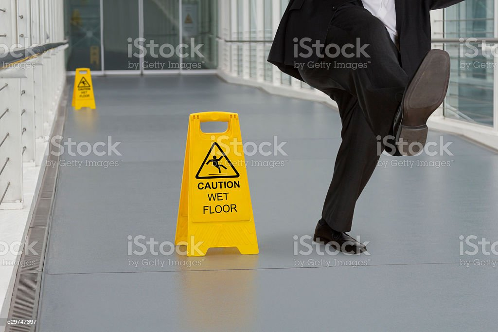 Man in suit slipping on wet floor stock photo