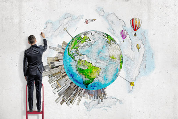 A man in suit standing on a ladder and painting planet Earth with high-rise buildings springing up on it. stock photo