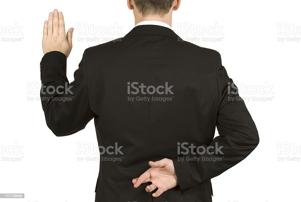 Man in suit taking oath while crossing fingers behind back stock photo