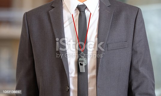 istock Man in suit wearing a whistle with red string. 3d illustration 1053136692