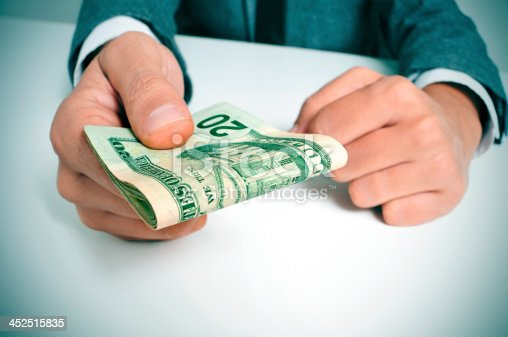 istock man in suit with a wad of american dollar bills 452515835