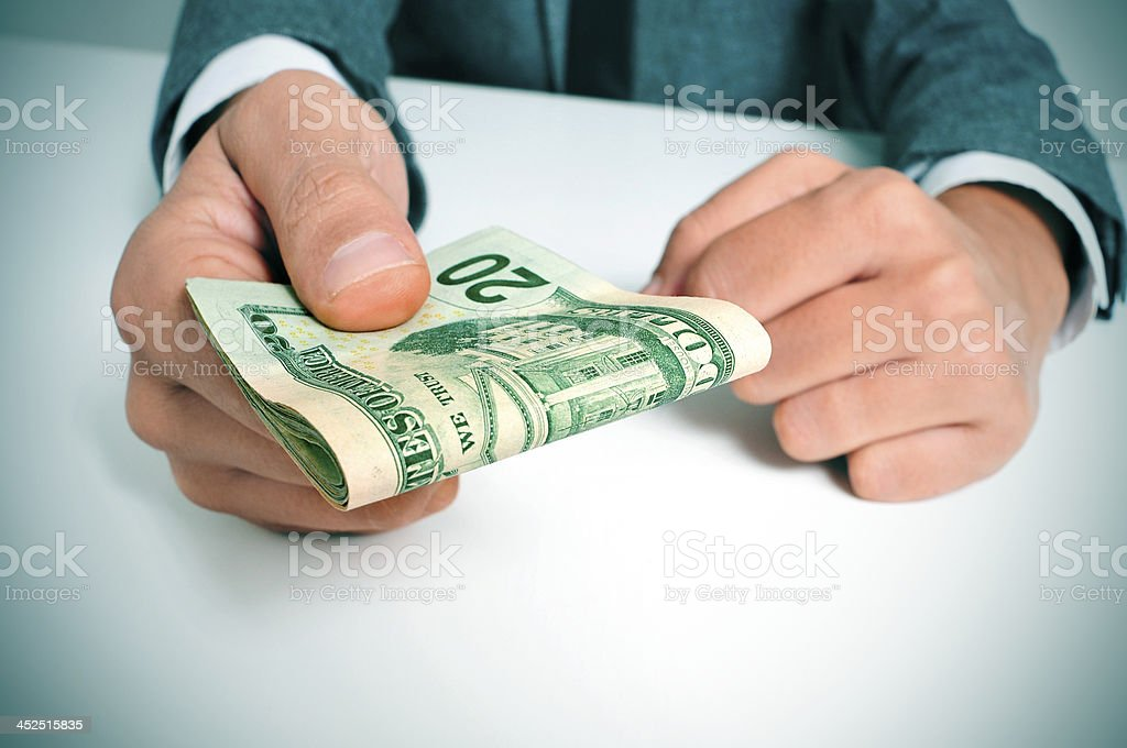 man in suit with a wad of american dollar bills stock photo