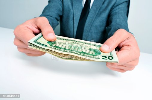 istock man in suit with a wad of american dollar bills 464538471