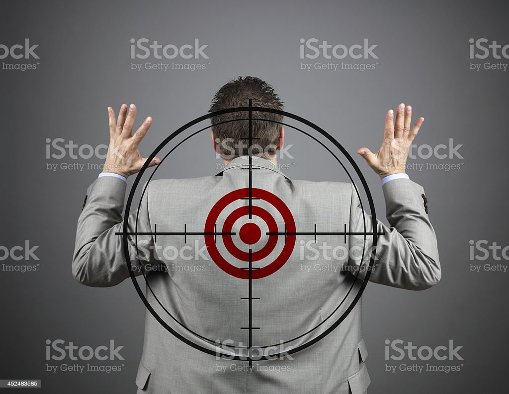 Man in suit with hands raised in surrender and target stock photo