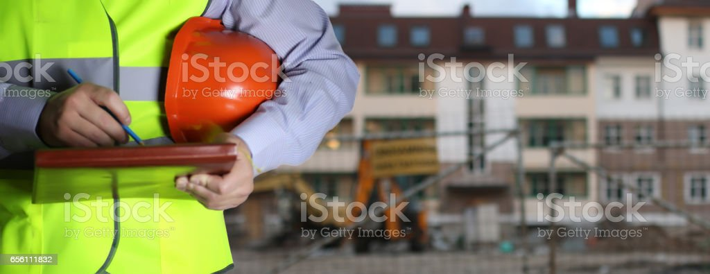 man in suit with helmet closeup in costruction area stock photo