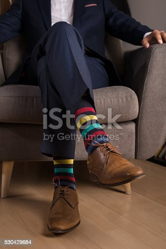 istock Man in suit with outstanding and funny colored socks 530429684