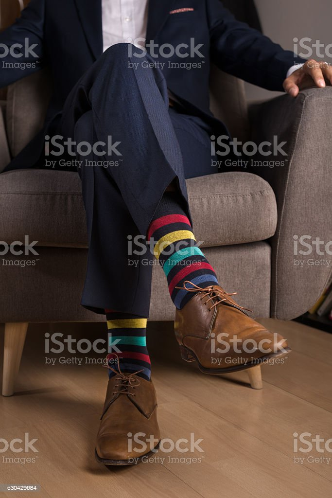 Man in suit with outstanding and funny colored socks stock photo