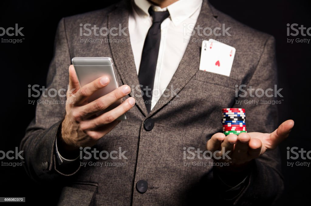 Man in suit with to aces in pocket, online poker stock photo