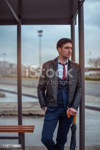 Man in suit with umbrella in his hand is  waiting in a bus stop - İmages