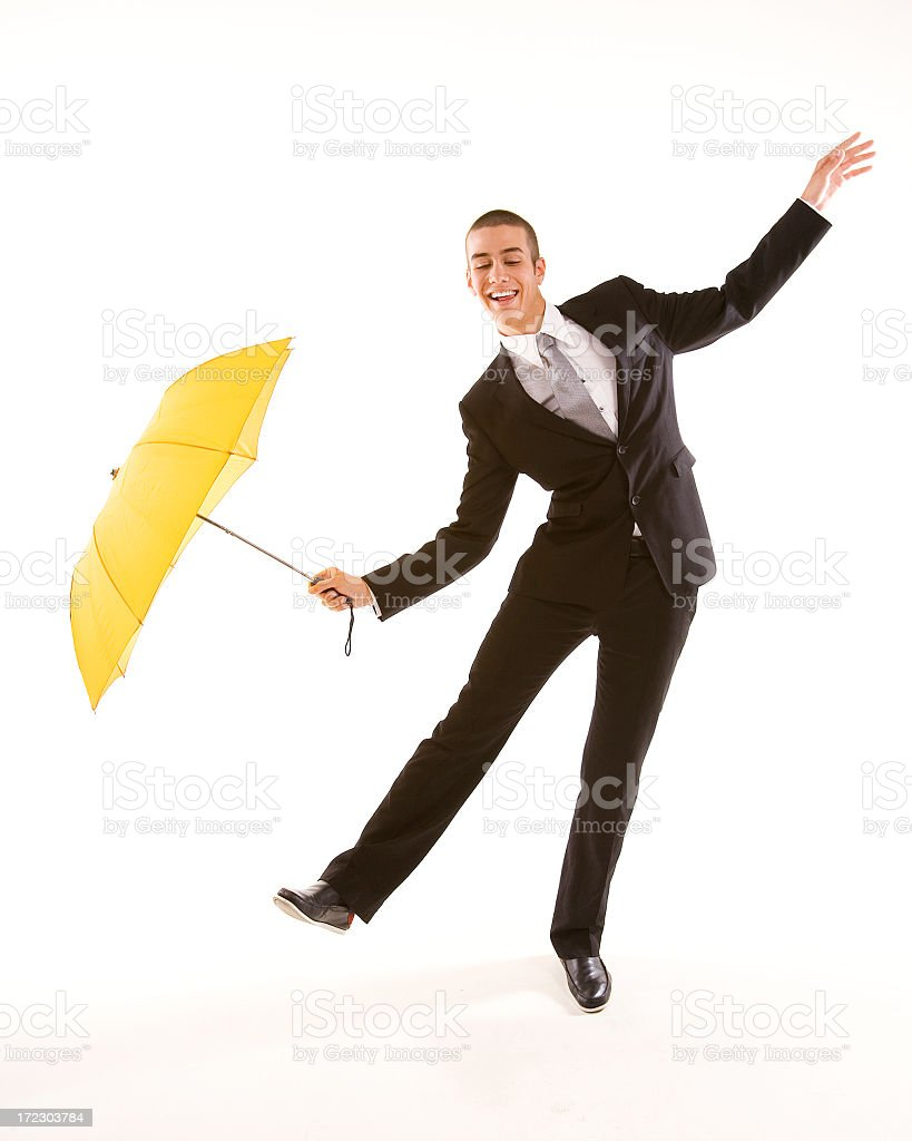 Man in suit with yellow umbrella doing funny business stock photo