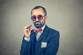 Handsome mature gentleman with cigar wearing checkered suit and sunglasses