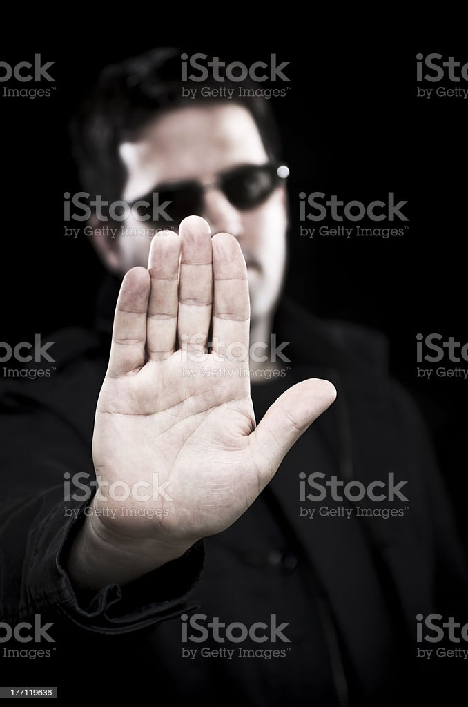 Man in sunglasses holds up hand royalty-free stock photo
