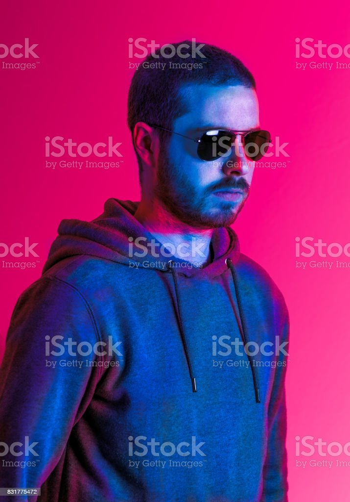 Man in sunglasses in pink light stock photo