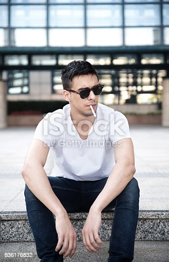 istock Man in sunglasses smoking cigarette 836176832