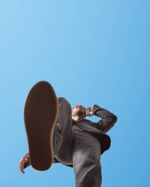 A man in sunglasses walks down the street and talks on the phone. Low angle. Blue sky in the background stock photo