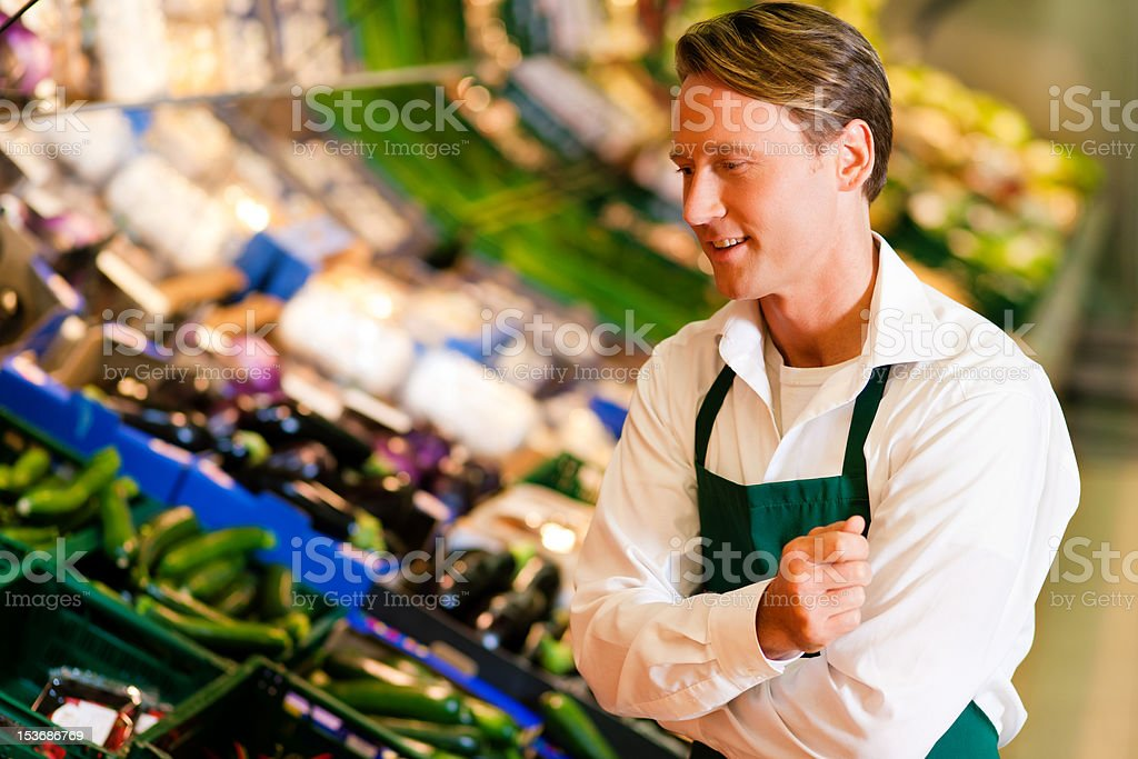 Man in supermarket as shop assistant royalty-free stock photo