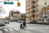 Two women in New York walks on the street in surgery face masks cross the road. Brooklyn, Bensonhurst.