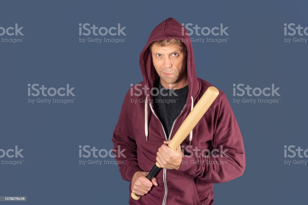 Portrait of a man in checkered scarf holding a baseball bat...
