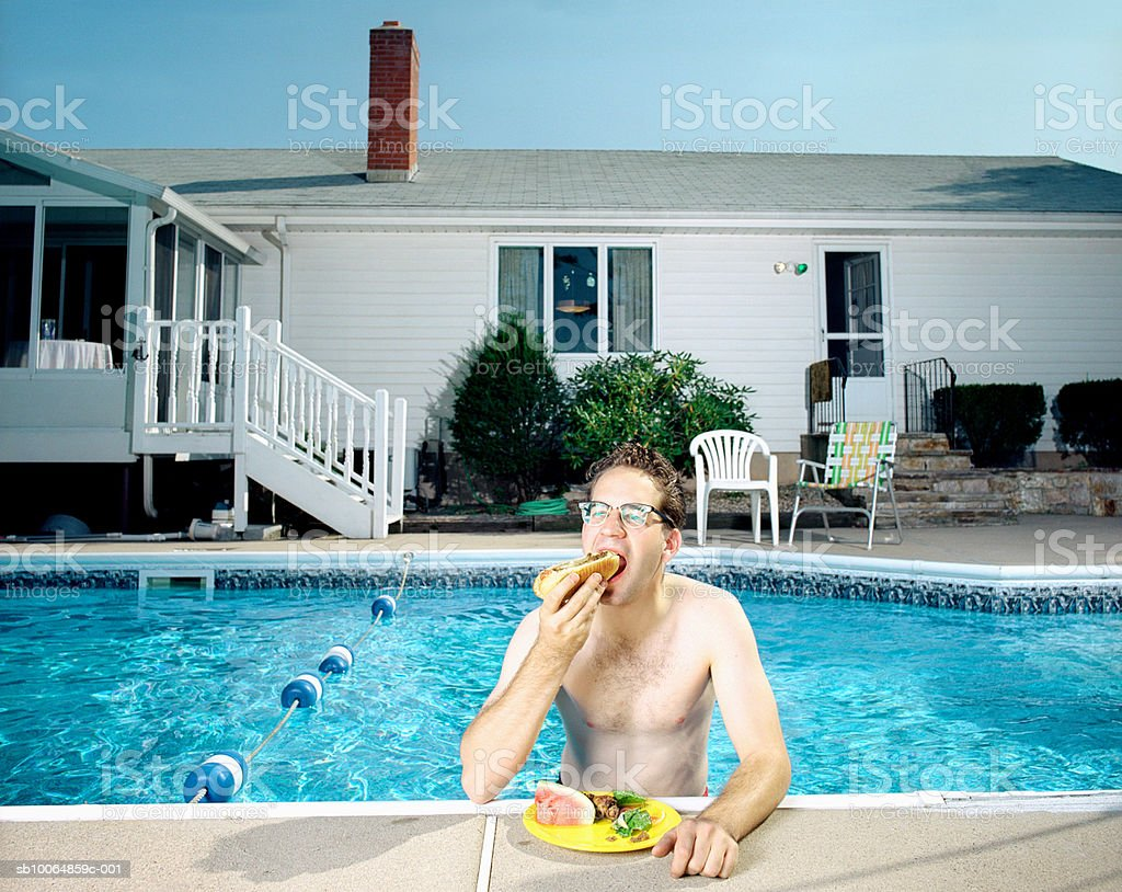 Man in swimming pool, eating hotdog Lizenzfreies stock-foto